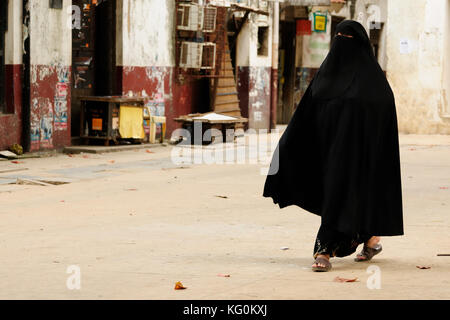 Muslim woman in the street of African city dressed in the chador - Stock Photo
