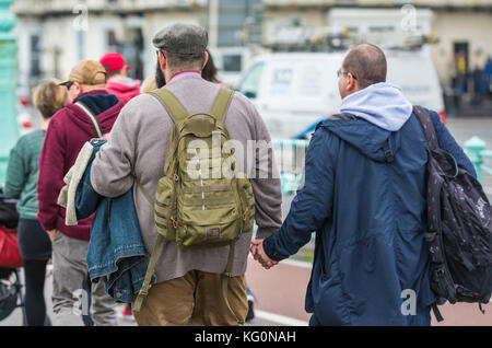 Couple of middle aged men holding hands in Brighton, East Sussex, England, UK. - Stock Photo