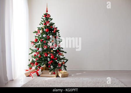 Christmas tree with red decorations new year gifts - Stock Photo