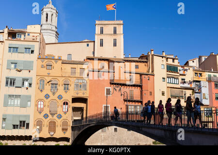 A group of girls cross a bridge over the River Onyar with the historic coloured houses of Old Town Girona, Catalonia, - Stock Photo