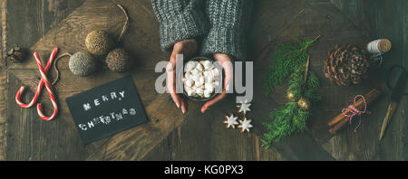 Flat-lay of greeting card, woman's hands holding mug, pine cone - Stock Photo