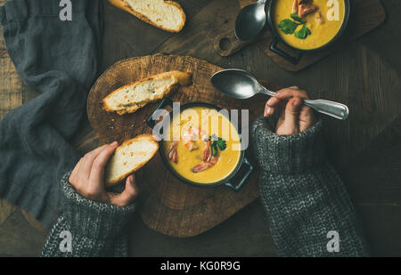 Woman in sweater eating corn soup with prawns, top view - Stock Photo