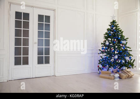Christmas tree with blue in a white room with toys for Christmas - Stock Photo