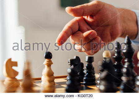 Closeup of a man pointing to the Chess figure - Stock Photo