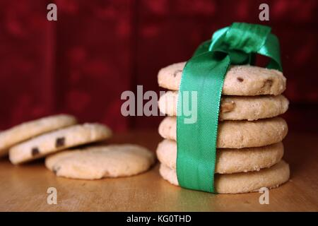 Selection of choc chip and fruit cookies, wrapped in a green ribbon, on a wooden table with a festive red background - Stock Photo