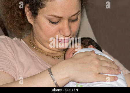 Mother holding her girl baby and touching her back - Stock Photo