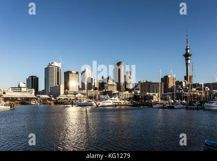 Sunset over the Auckland financial district and the sky tower in New Zealand largest city. - Stock Photo