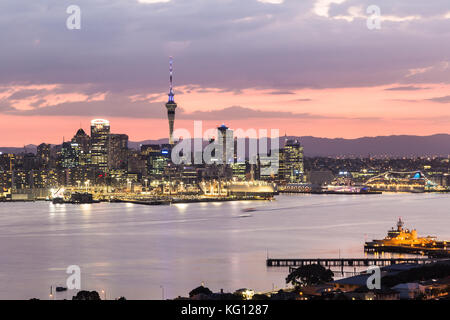 Sunset over Auckland central business district skyline and the harbor taken from the Davenport hill viewpoint in - Stock Photo