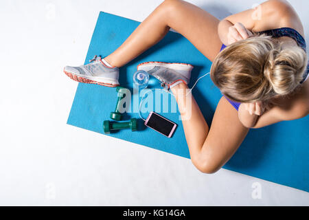 Female fitness model resting after an intense workout and taking some a selfie in the mirror of the gym. - Stock Photo
