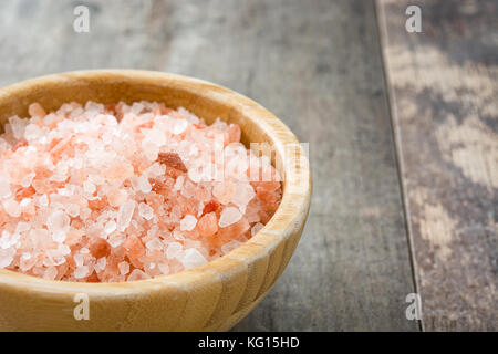 Himalayan salt in bowl on wooden table - Stock Photo