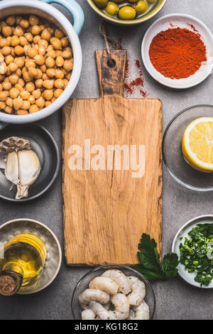 Cooked Chickpeas and various Healthy  ingredients for salad around wooden cutting board, top view - Stock Photo