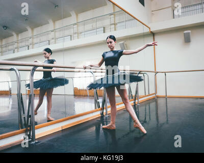 Ballerina in black tutu and pointe stretches on barre in ballet gym. Woman standing near bar and mirror, preparing - Stock Photo