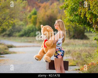 Teen girl standing waiting on country-road for somebody big teddy-bear in hand suitcase short mini-skirt miniskirt - Stock Photo