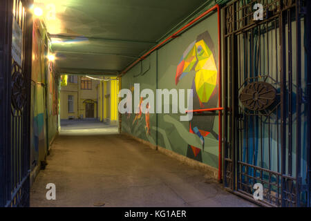 St. Petersburg, Russia - June 23, 2016: Illuminated arch with street art in old apartment building - Stock Photo