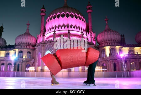 Brighton, UK. 2nd Nov, 2017. Ice skating brother and sister Sophia (12) and Curtis (13) Elton pull a giant cracker - Stock Photo