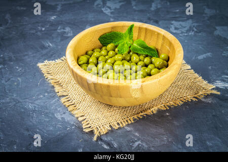 Canned peas in a wooden plate on a gray concrete background - Stock Photo