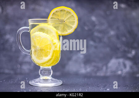 Homemade lemonade in a glass with a handle on a gray concrete background. Water with slices of lemon on a dark background. - Stock Photo