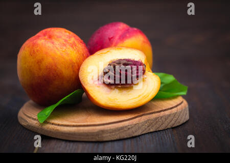 Ripe plums and nectarines on a wooden table. Ripe fruit on a rough wooden background. Rustic cuisine. - Stock Photo
