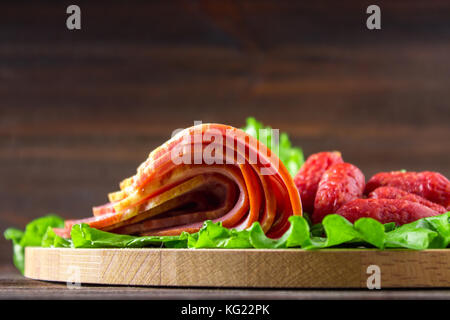 Assorted meat products including ham and sausages. - Stock Photo