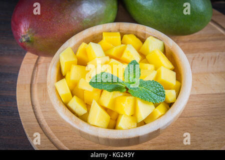 Tropical fruit mango in a plate on a wooden background, whole or sliced - Stock Photo
