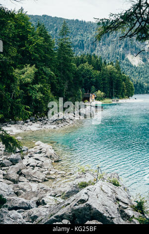 Rocks on the shore of the Eibsee mountain lake in the Alps in southern Germany - Stock Photo