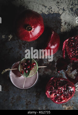 Alcoholic cocktail garnished with pomegranate seeds on dark moody background - Stock Photo