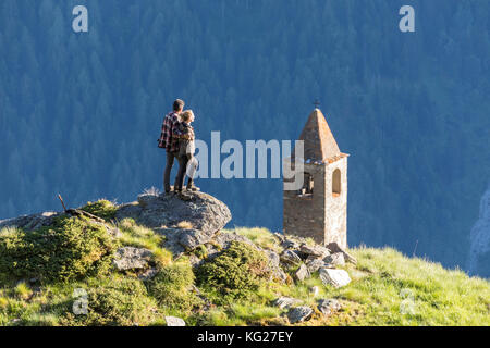 Man and woman embraced look at the bell tower, San Romerio Alp, Brusio, Poschiavo Valley, Canton of Graubunden, - Stock Photo