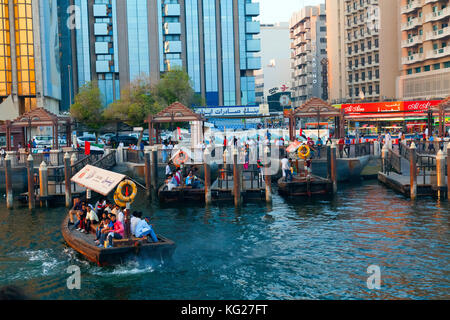 A water taxi carrying passengers arrives at a busy dock, Dubai Creek, Dubai, United Arab Emirates, Middle East - Stock Photo