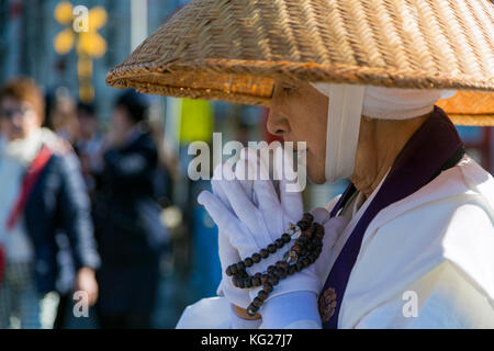Japanese female Buddhist monk collecting alms at the Kiyomizudera Temple in Kyoto, Japan, Asia - Stock Photo