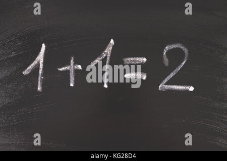 Math simple equation on chalk board. One plus One equals two. - Stock Photo