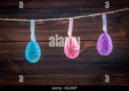 Easter holiday background with eggs decorations hanging on rope - Stock Photo