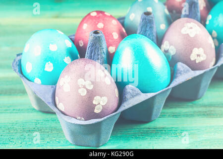 Violet and blue Easter eggs in cardboard trays. Blue wooden background. Happy easter - Stock Photo