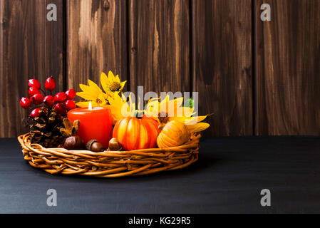 Autumn arrangement decoration in a tray with candle,pumpkins, yellow flowers, pine-cones, acorns , berries  on wooden - Stock Photo