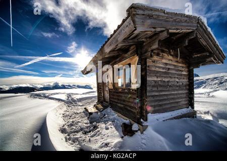 Wooden mountain hut in winter mountain scenery - Stock Photo