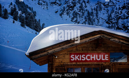 snow covered roof of ski school hut - Stock Photo