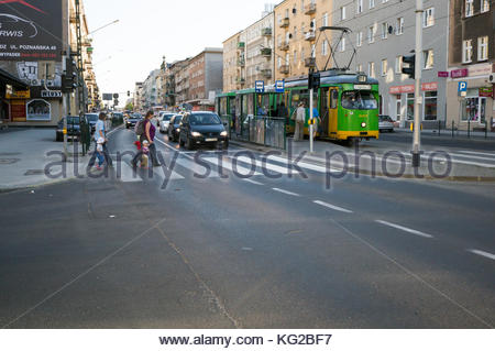 People on the zebra crossing at the busy Glogowska street in Poznan, Poland - Stock Photo