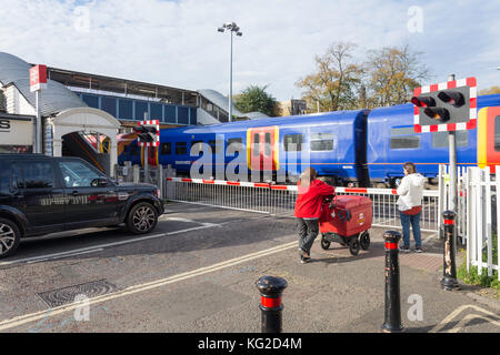 Railway crossing barriers working at Mortlake Train Station, Mortlake, London Borough of Richmond upon Thames, Greater - Stock Photo