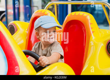 Little baby boy riding car in amusement park - Stock Photo