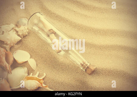Message in bottle on the beach. Summer background with hot sand, in vintage style - Stock Photo