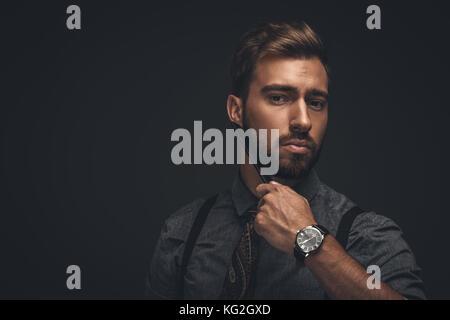 Handsome man combing beard - Stock Photo
