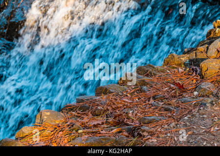 Spillway waterfall and stone edge closeup in sunny autumn day - Stock Photo