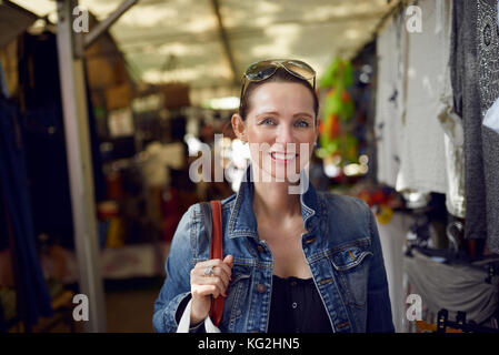 Happy attractive stylish woman shopping at an outdoor market standing looking at the camera with a wide warm friendly - Stock Photo