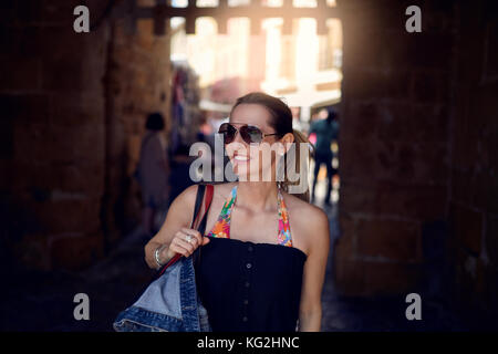 Attractive trendy woman wearing sunglasses and carrying a large handbag over her shoulder shopping in town looking - Stock Photo