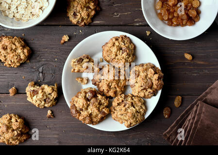 Tasty healthy oatmeal cookies on plate over wooden background, top view - Stock Photo