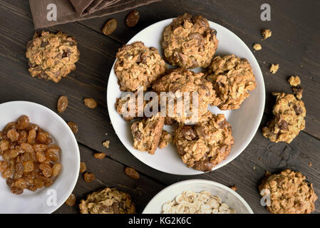 Cookies for breakfast on plate over wooden background, top view - Stock Photo