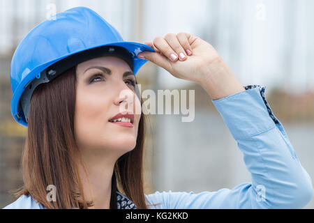 Beautiful woman architect wearing helmet at construction site - Stock Photo