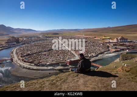 Baiyu,China-October 17,2017; Monks sitting on mountain at morning in Yarchen Gar monasterry a famous Lamasery in - Stock Photo