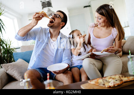 Happy family sharing pizza together at home - Stock Photo