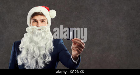 A businessman with a beard in a Santa Claus hat holds a credit c - Stock Photo