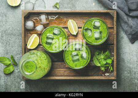 Fresh green smoothie with ice cubes, mint, lime in tray - Stock Photo